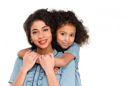 daughter embracing her smiling mother from behind isolated on white