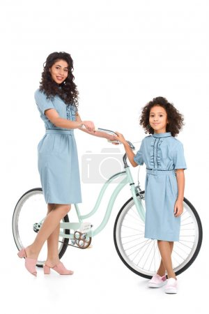 mother and daughter standing with bicycle isolated on white