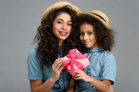 beautiful mother and daughter with pink gift box for mothers day isolated on grey