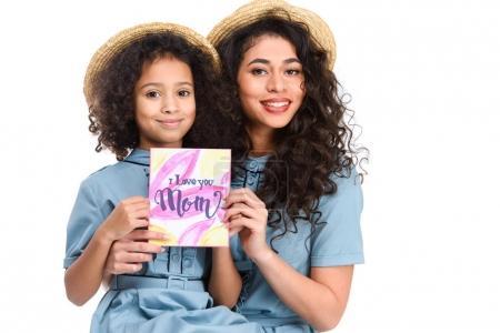 heureuse mère et fille avec carte de voeux de jour de mères en regardant caméra isolé sur blanc