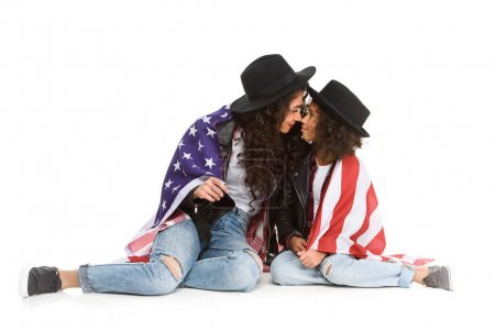 beautiful mother and daughter covered in usa flag sitting on floor isolated on white