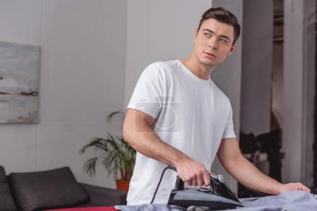 handsome man ironing shirt on ironing board in living room and looking away