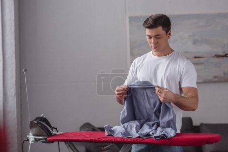 Photo for Handsome man holding shirt for ironing in living room - Royalty Free Image