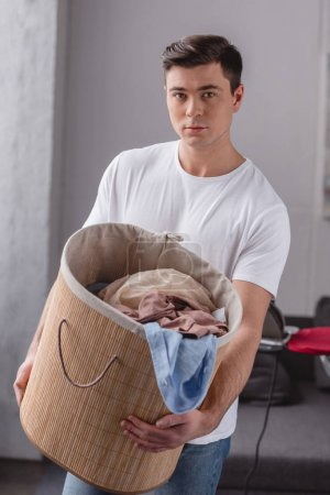 handsome man holding basket with laundry and looking at camera