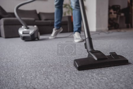 Photo for Cropped image of man cleaning carpet in living room with vacuum cleaner - Royalty Free Image