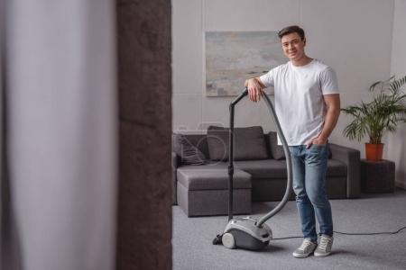 handsome man leaning on vacuum cleaner in living room