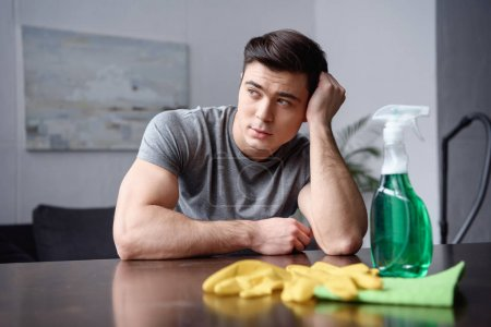 handsome man sitting at table with cleaning stuff and looking away in living room