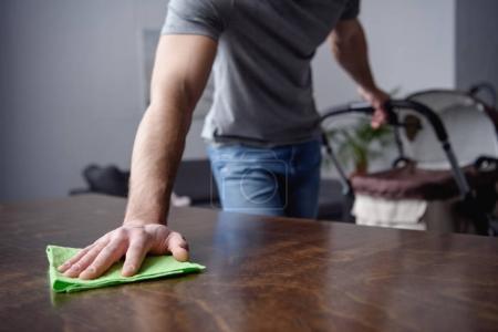 Photo pour Image recadrée de l'homme, dépoussiérage tableau avec chiffon et tenant le landau avec l'autre main dans le salon - image libre de droit