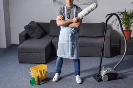 Photo pour Image recadrée de l'homme debout et tenant la brosse pour nettoyer la poussière dans le salon - image libre de droit