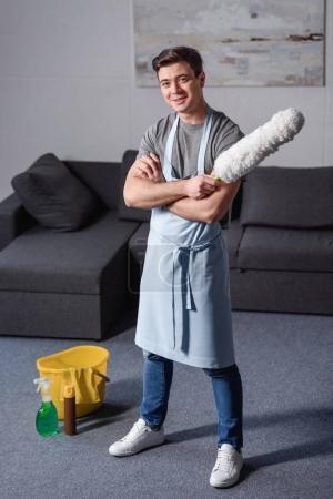 Photo pour Bel homme debout en souriant et en tenant la brosse pour nettoyer la poussière dans le salon - image libre de droit