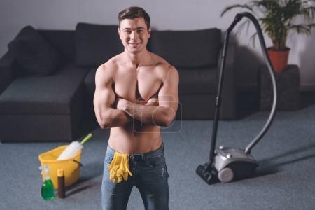 Foto de Sonriente hombre camisa sexy de pie con los brazos cruzados, guantes de goma en jeans - Imagen libre de derechos