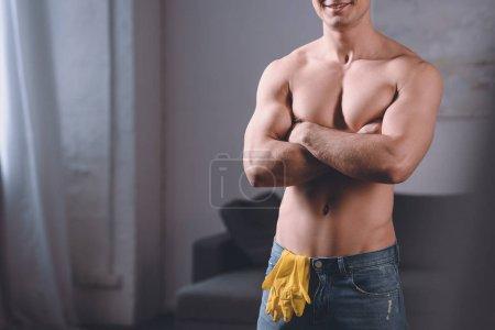 Photo pour Image recadrée de séduction homme torse nu debout avec les bras croisés, gants en caoutchouc en jeans - image libre de droit