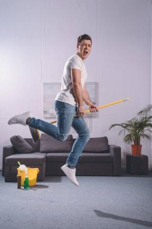 handsome man jumping with broom in living room