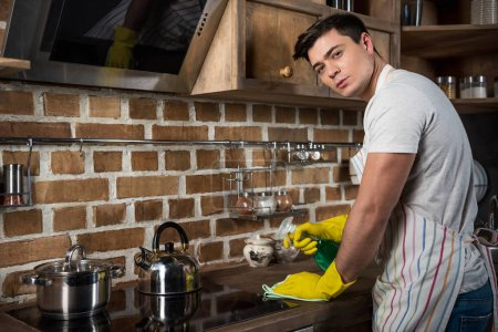 handsome man cleaning kitchen with spray bottle and rag and looking at camera