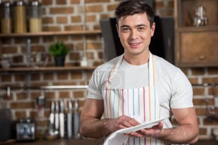 handsome man wiping plate with towel and looking at camera at kitchen