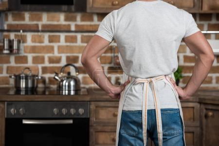 cropped image of man standing in apron at kitchen