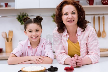 grandmother and little granddaughter sitting together at kitchen and looking at camera