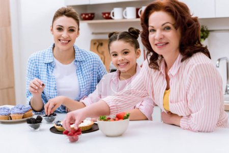 three generations of women decorating dessert with berries together at kitchen and looking at camera