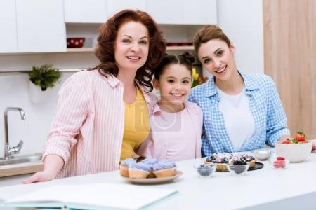 three generations of women with desserts at kitchen looking at camera