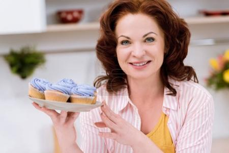 close-up portrait of beautiful mature woman with plate of blueberry cupcakes at kitchen