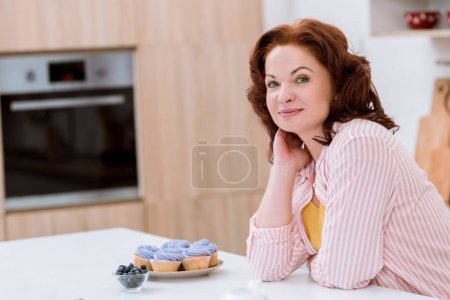 happy mature woman with plate of blueberry cupcakes at kitchen