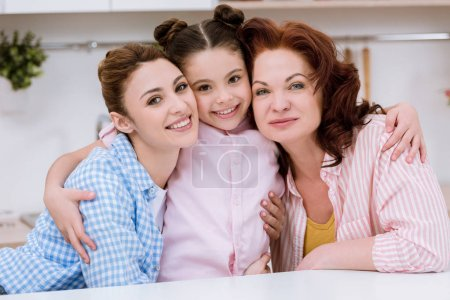three generations of women embracing and looking at camera