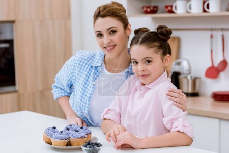 happy young mother and daughter with blueberry cupcakes at kitchen