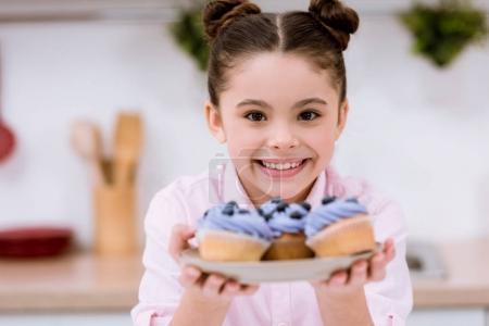 entzückendes kleines Kind hält Teller mit Blaubeer-Cupcakes