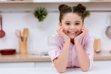 adorable little child at kitchen looking at camera