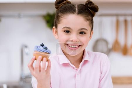 close-up portrait of little child holding blueberry cupcake