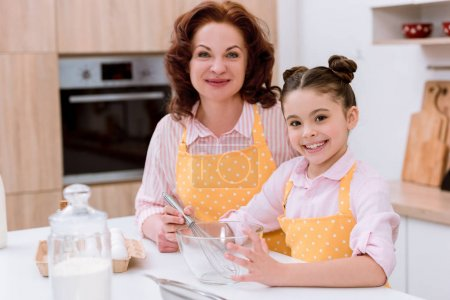 happy grandmother with little granddaughter cooking together and looking at camera