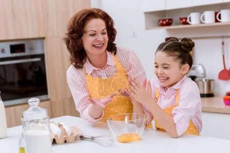 happy grandmother with little granddaughter preparing dough for cooking at kitchen