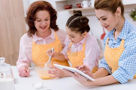 grandmother and granddaughter cooking together while mother using tablet at kitchen