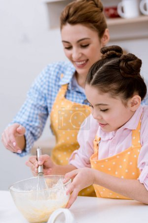 happy mother and daughter mixing dough together