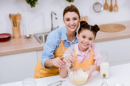 Photo for Mother and daughter mixing dough for pastry at kitchen - Royalty Free Image