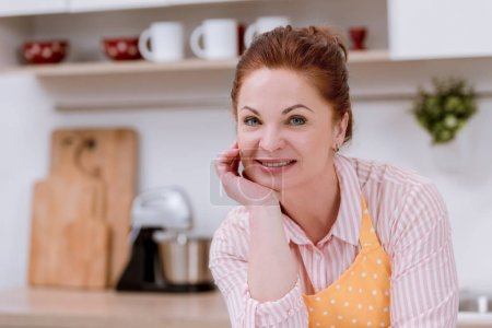 close-up portrait of smiling mature woman in apron at kitchen and looking at camera