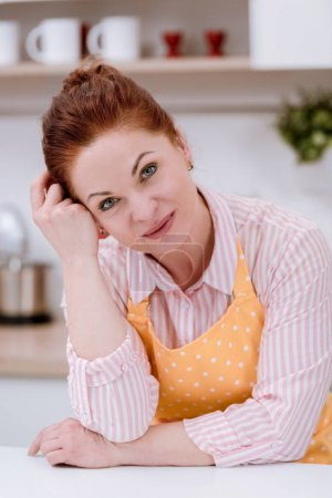 close-up portrait of beautiful mature woman in apron at kitchen and looking at camera
