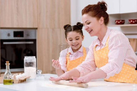 grandmother with little granddaughter rolling dough for cookies