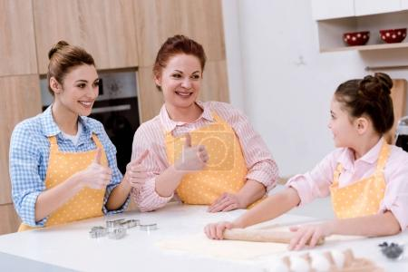 grandmother and mother showing thumbs up to daughter while she preparing dough for cookies at kitchen