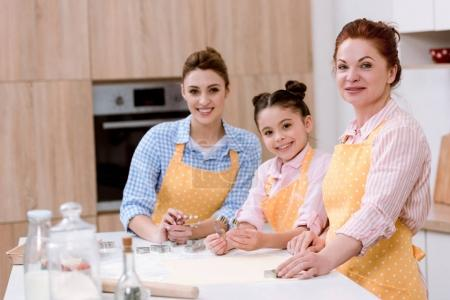 three generations of women cooking together at kitchen