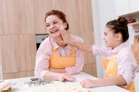 happy grandmother and little granddaughter playing with flour at kitchen while cooking