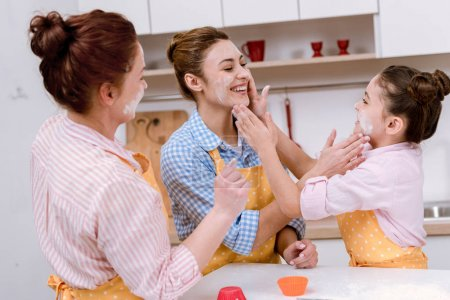 three generations of happy women playing with flour at kitchen