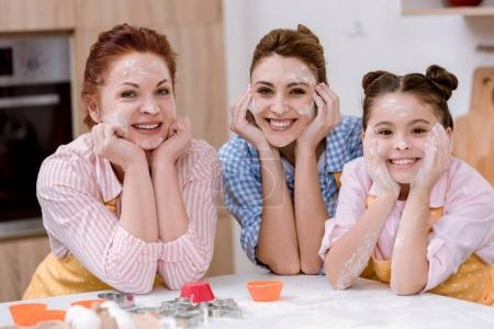 three generations of women in aprons with flour on faces at kitchen and looking at camera