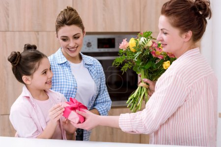 mother and grandmother presenting gift and flowers to daughter