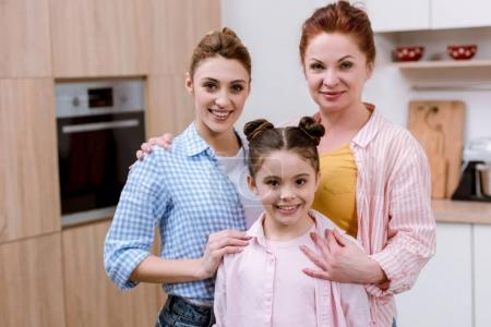 Photo for Three generations of women standing together at kitchen and looking at camera - Royalty Free Image