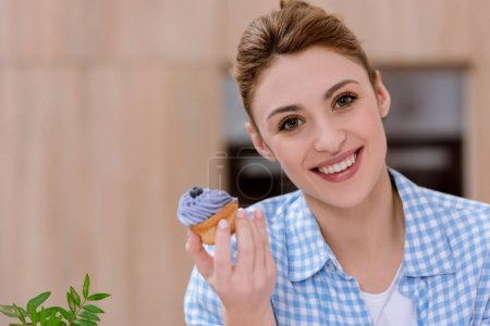 attractive young woman with creamy cupcake looking at camera