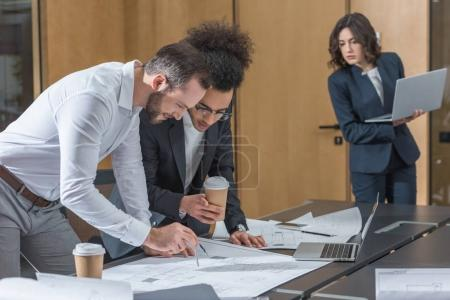team of architects working with building plans at conference hall of office