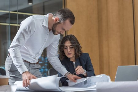 Photo for Professional architects working with building plans together at office - Royalty Free Image
