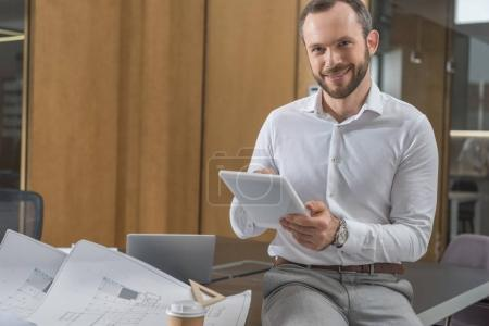 handsome happy architect sitting on table with plans and using tablet at office