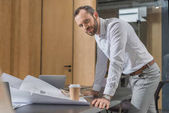 handsome happy architect working with building plans at office